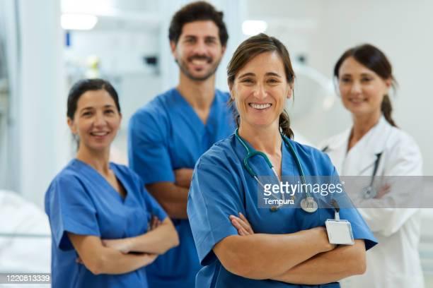 retrato de una enfermera adulta media con su equipo de pie sobre el fondo. - asistencia sanitaria y medicina fotografías e imágenes de stock