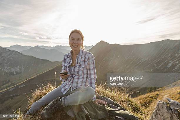 Portrait of a mid adult woman backpacker with smartphone, Achensee, Tyrol, Austria