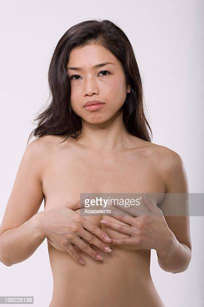 Portrait of a mid adult woman covering her breast