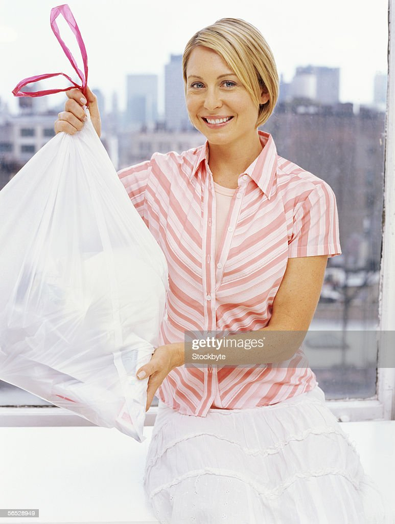 portrait of a mid adult woman holding a garbage bag : ストックフォト