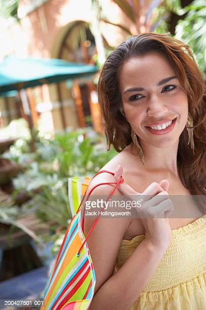 Portrait of a mid adult woman holding a shopping bag over her shoulder and smiling