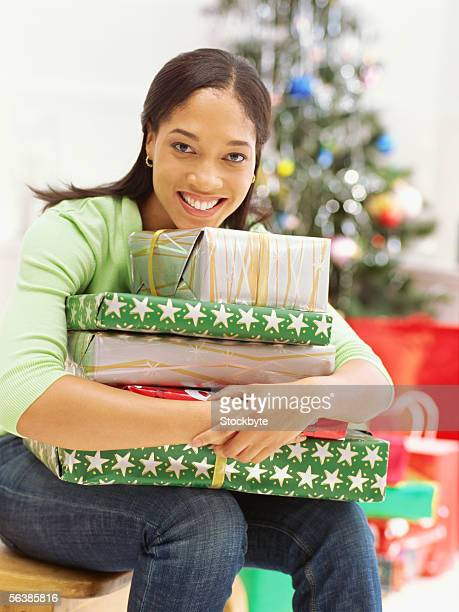 portrait of a mid adult woman hugging christmas gifts