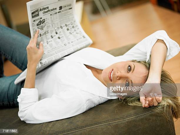 Portrait of a mid adult woman lying on the bed and holding a newspaper