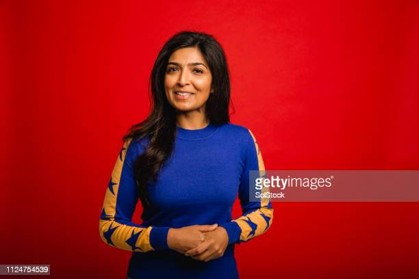 portrait of a mid adult woman - red background stock pictures, royalty-free photos & images