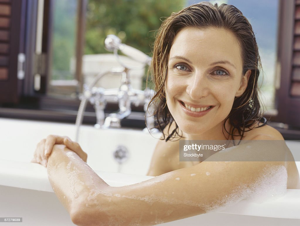 Portrait of a mid adult woman sitting in a bathtub and smiling : Stock Photo