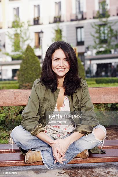 portrait of a mid adult woman sitting on a park bench and smiling - 黒髪 ストックフォトと画像
