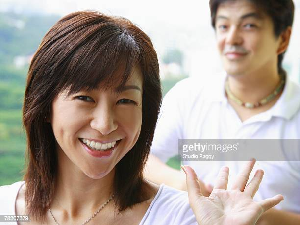 portrait of a mid adult woman smiling with a mid adult man standing in the background - mid length hair stock pictures, royalty-free photos & images