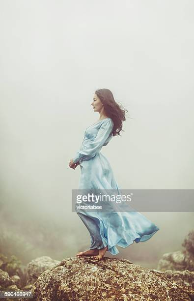portrait of a mid adult woman standing on rocks in the mist - long dress stock pictures, royalty-free photos & images