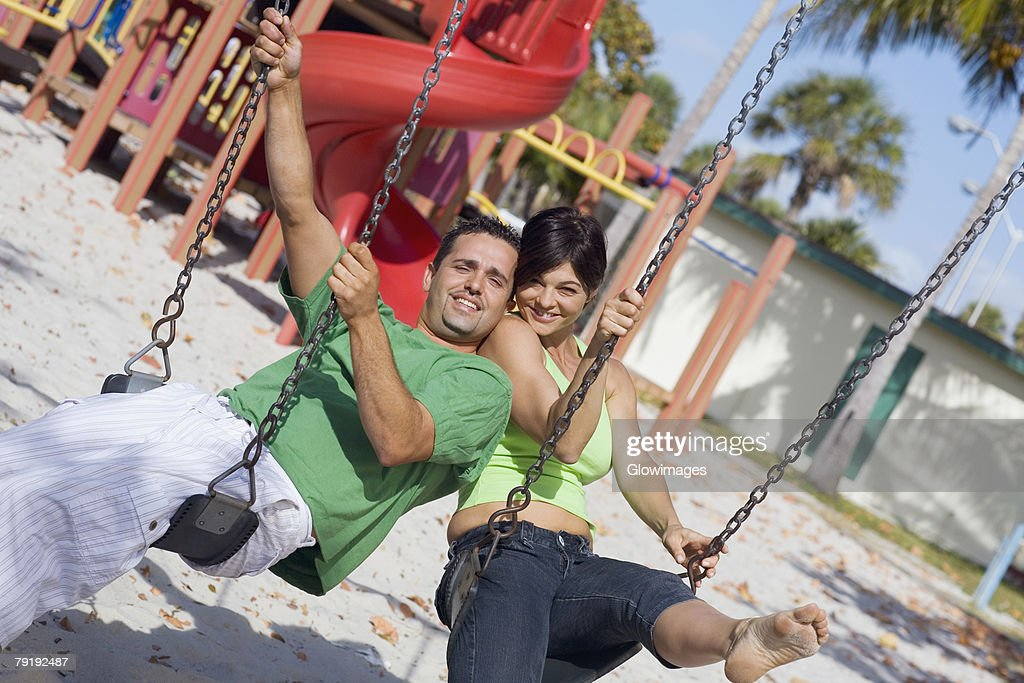 Portrait of a mid adult woman swinging on a swing with her husband : Foto de stock