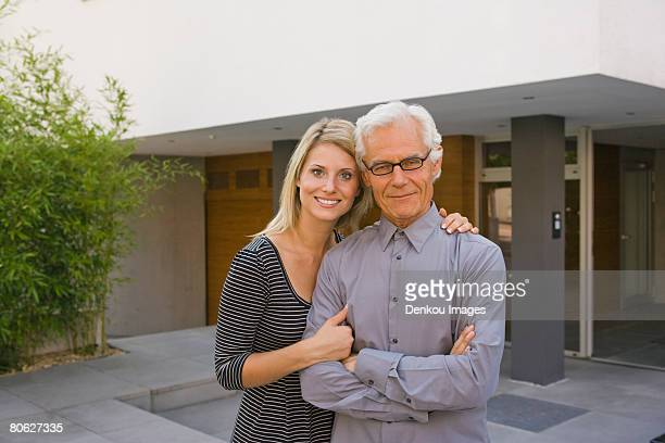 Portrait of a mid adult woman with arm around her father and smiling