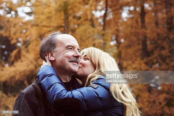 portrait of a mid-aged woman kissing her senior father on the cheek in a park