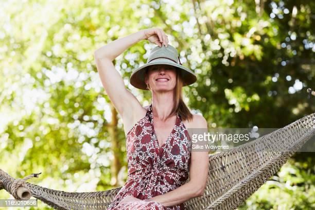 portrait of a middle aged happy woman sitting in a hammock wearing with a straw hat - alles hinter sich lassen stock-fotos und bilder