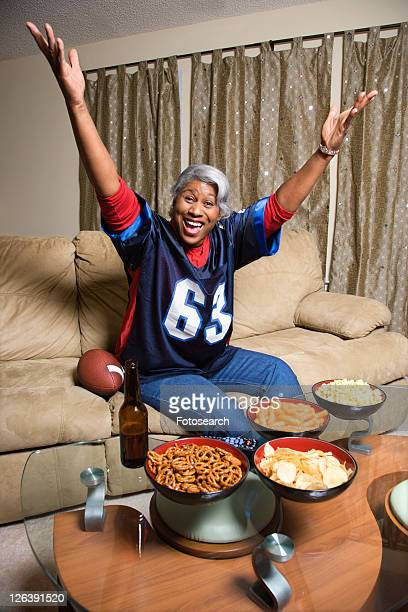 portrait of a middle-aged african-american woman wearing a football jersey with hands in the air watching football game. - sports jersey stock pictures, royalty-free photos & images