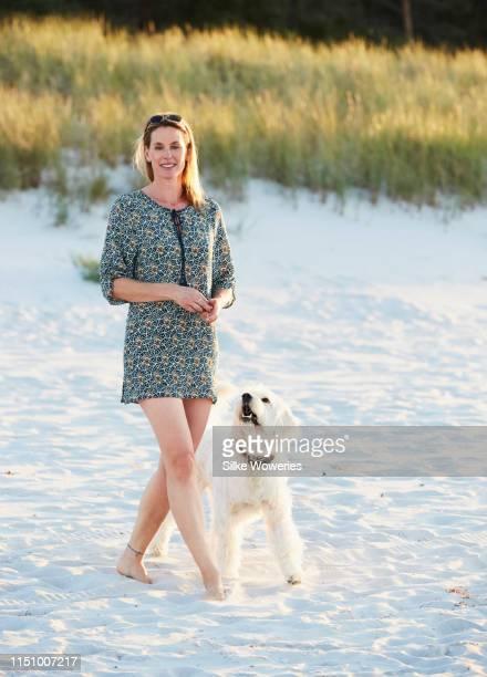 portrait of a middle-aged woman at the beach walking her dog - aktiver lebensstil stock-fotos und bilder
