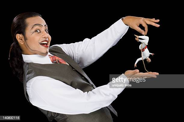 Portrait of a mime holding a rope with two acrobat performing on it