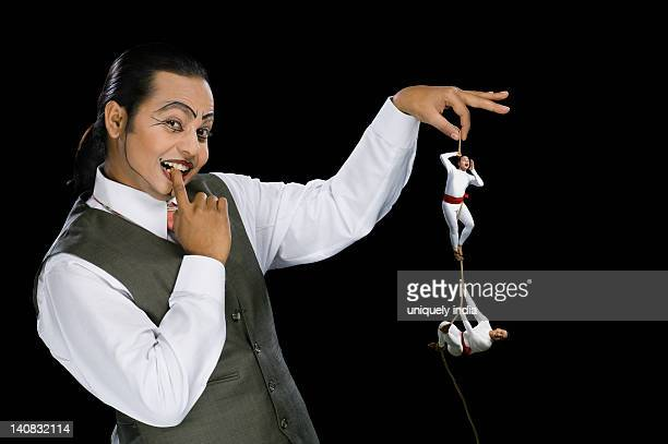 Portrait of a mime holding a rope with two acrobats performing on it