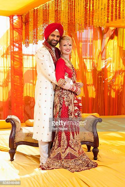 Portrait of a mixed race couple on their wedding day in traditional indian garments for a wedding; ludhiana punjab india