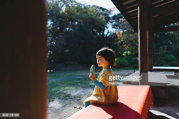 Portrait of a mixed race little girl eating ice cream bar