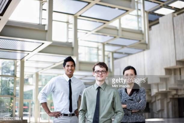 A portrait of a mixed race team of business people standing in the lobby area of a convention centre.