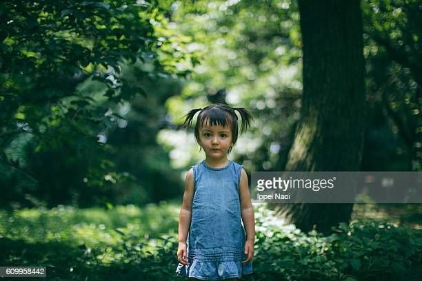 Portrait of a mixed race toddler girl looking at camera in park