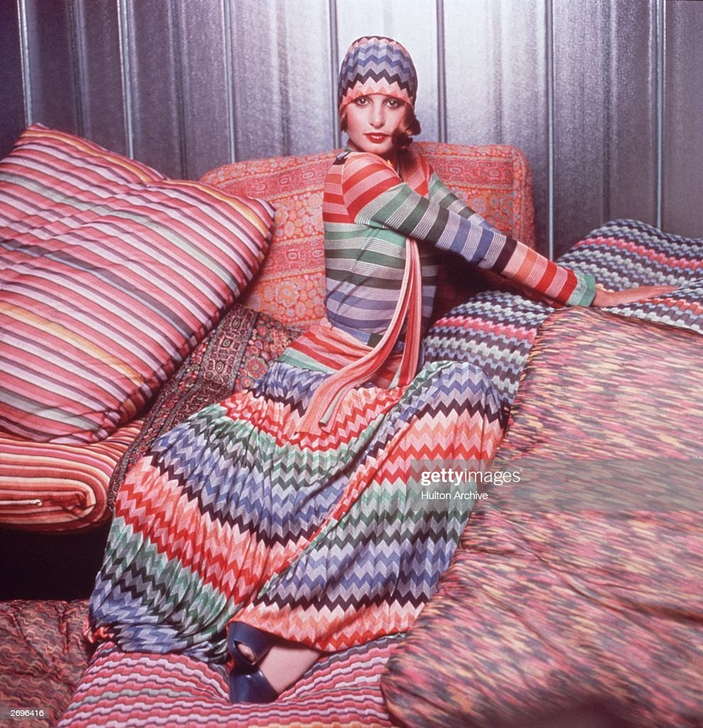 Portrait of a model wearing a colorful outfit designed by Missoni while posing on pillows covered in Missoni fabric. The outfit consists of a herringbone weave head scarf and maxi skirt and a striped top.