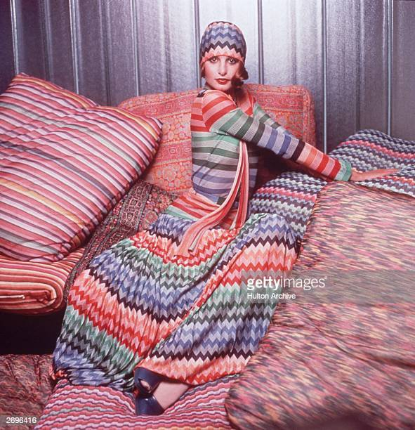 Portrait of a model wearing a colorful outfit designed by Missoni while posing on pillows covered in Missoni fabric The outfit consists of a...