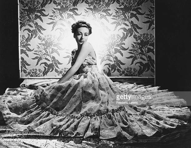 Portrait of a model wearing a dress belonging to actress Joan Crawford with the skirt of the gown laid out around her like a flower circa 1965