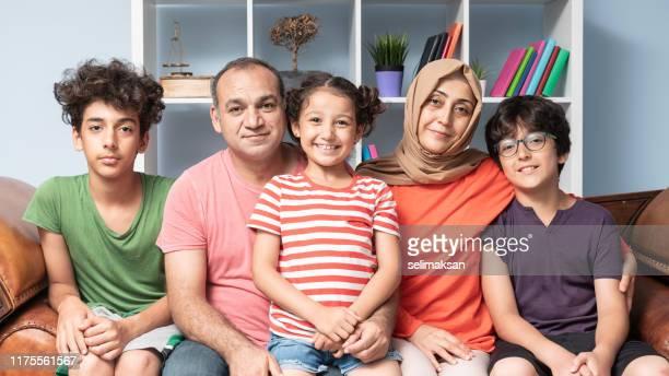 porträt einer modernen muslimischen familie im wohnzimmer - türkei stock-fotos und bilder