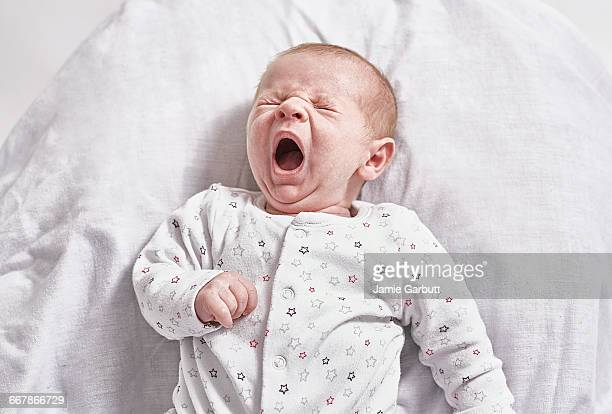 a portrait of a month old baby yawning - newborn stock pictures, royalty-free photos & images