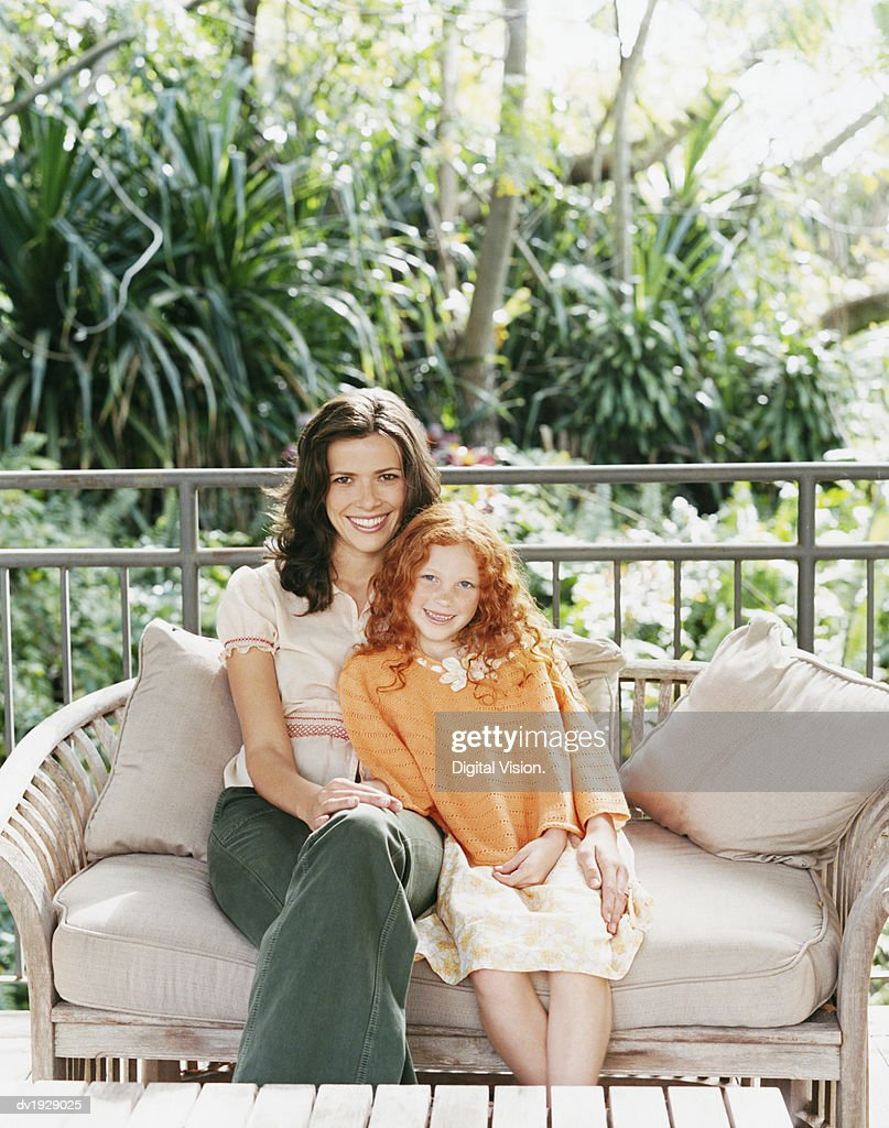 Portrait of a Mother and a Daughter Sitting on a Sofa on Their Porch : Stock Photo