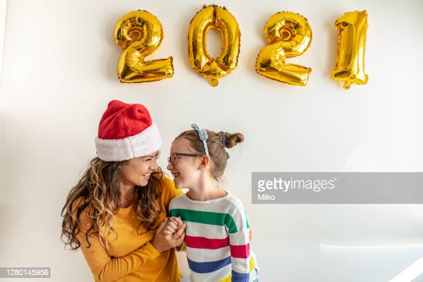 a portrait of a mother and daughter celebrating the new year - 2021 stock pictures, royalty-free photos & images