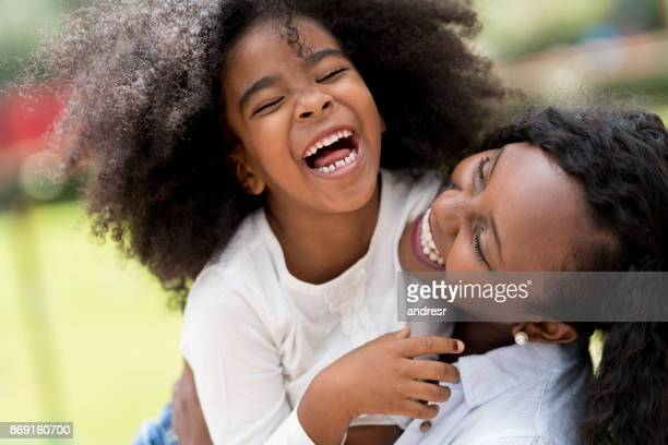 portrait of a mother and daughter having fun outdoors - funny black girl stock photos and pictures
