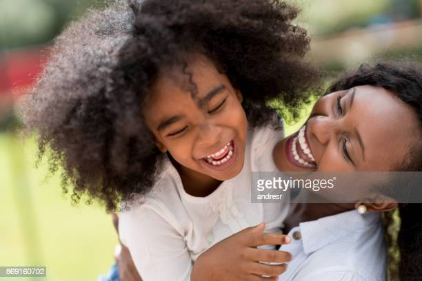 portrait of a mother and daughter looking very happy outdoors - funny black girl stock photos and pictures