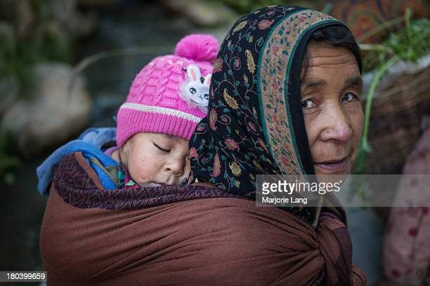 Portrait of a mother and her baby sleeping in her back in the Baltistan village of Turtuk, formerly part of Pakistan until 1971. Nubra valley,...