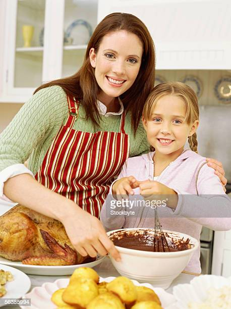 portrait of a mother cooking with her daughter