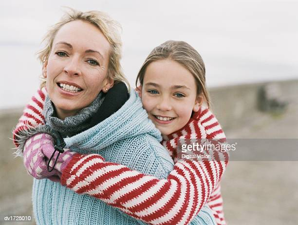 Portrait of a Mother Giving Her Daughter a Piggyback, With both Wearing Warm Clothing