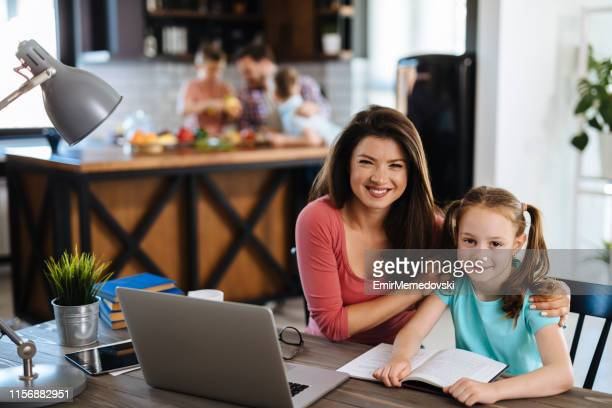 portrait of a mother helping her daughter with homework using laptop - incidental people stock pictures, royalty-free photos & images