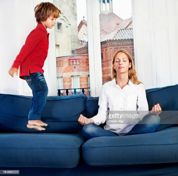 Portrait of a Mother Meditating and Her Son is jumping