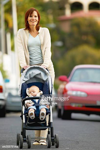 portrait of a mother taking her baby (12-18 months) for a walk in a buggy