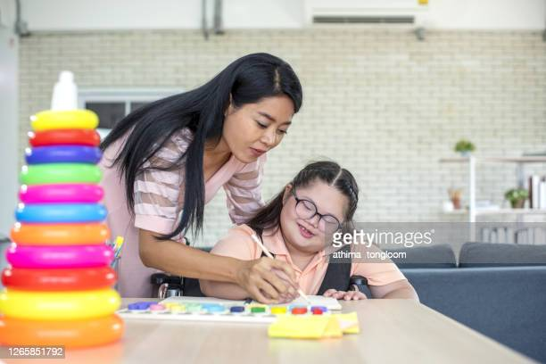 portrait of a mother with daughter autism and down syndrome in daily lives. - autism stock pictures, royalty-free photos & images