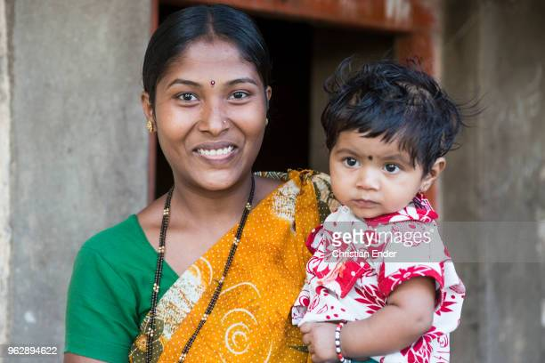 Portrait of a mother with her baby in front of a cottage She looks directly into the camera The baby on her arms looks curious Both are weared in...