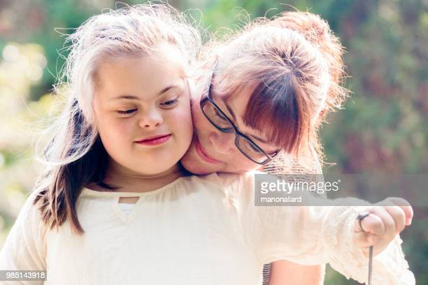 portrait of a mother with her daughter of 12 years old with autism and down syndrome in daily lives - autismo foto e immagini stock