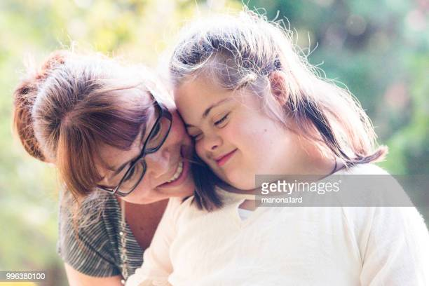 portrait of a mother with her daughter of 12 years old with autism and down syndrome in daily lives - down syndrome stock pictures, royalty-free photos & images