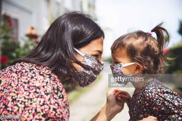 ritratto di madre con la figlia piccola che indossa una maschera chirurgica - 2 3 anni foto e immagini stock