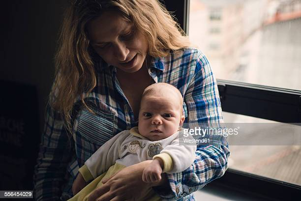 Portrait of a mother with her newborn baby sitting next to a window