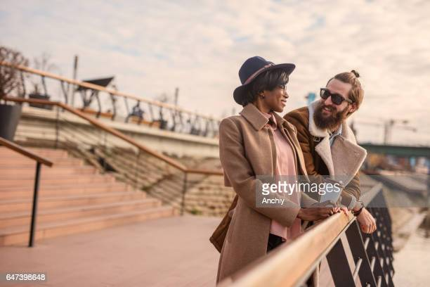 Portrait of a multi-ethnic couple leaned on a fence. Unshaven guy with his stylish female friend went out on a coffee outdoors