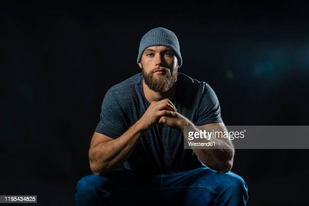 portrait of a muscular man sitting in studio - hero and not superhero stock pictures, royalty-free photos & images