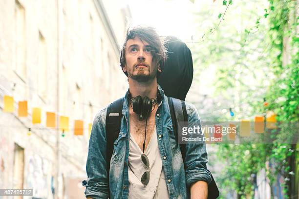portrait of a musician walking down the street - guitar case stock pictures, royalty-free photos & images