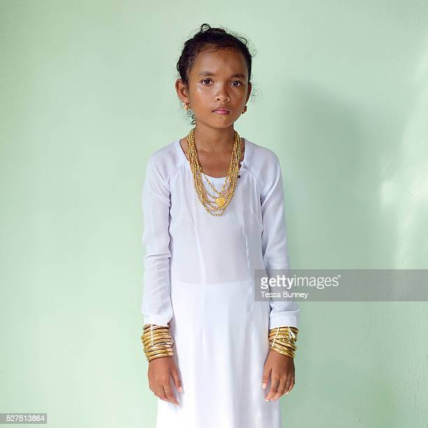 Portrait of a Muslim Cham girl wearing a white dress and bronze and copper jewellery at her Karoh ceremony in Van Lam Ninh Thuan province Central...