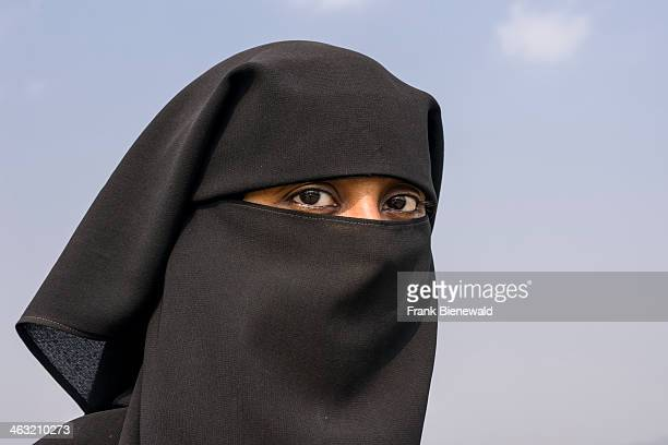 A portrait of a Muslim woman dressed in the traditional black burka including the hijab